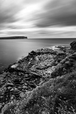 A black and white long exposure shot of the view from the Brough of Birsay, looking over to Marwick Head, Orkney, Scotland.